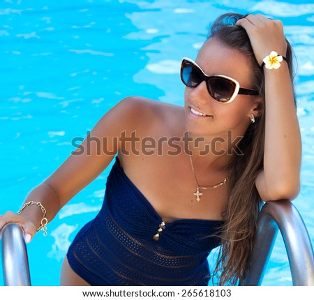 Shot of a teen girl enjoying a day at the luxury poolside, tanning. Girl at travel spa resort pool. Summer luxury vacation.