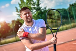 Shot of a tennis player with a shoulder injury on a clay court