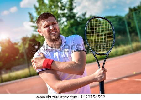 Shot of a tennis player with a shoulder injury on a clay court #1120756592