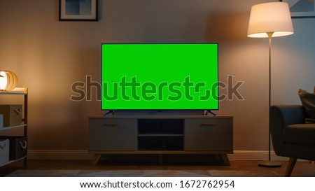 Photo of  Shot of a TV with Horizontal Green Screen Mock Up. Cozy Evening Living Room with a Chair and Lamps Turned On at Home.