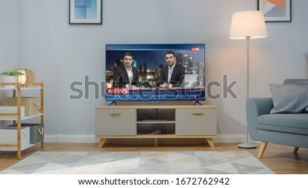 Shot of a TV with Live News Channel. Cozy Living Room at Day Time with a Chair and Lamps Turned On at Home.