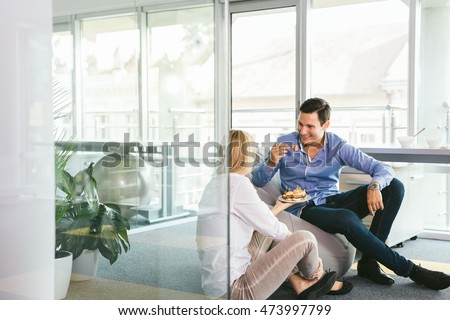 Shot of a two young business people gazing affectionately at each other in office #473997799