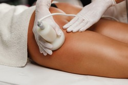Shot of a unrecognizable woman getting a anti cellulite massage at the beauty salon. She have a ultrasound cavitacion treatment to fat reduction.
