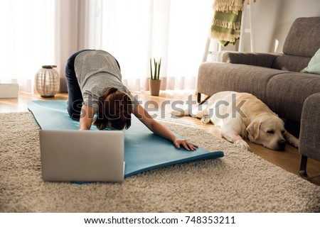 Shot of a woman doing exercise at home with her dog