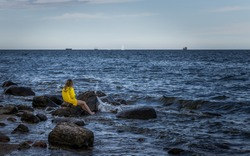 Shot of a woman staring at sea. She's feeling moody and dreamy. The girl sat down on a rock to rest