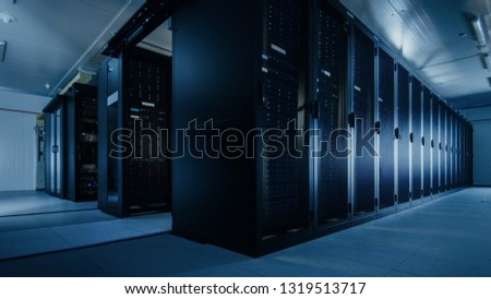 Shot of a Working Data Center With Rows of Rack Servers. Led Lights Blinking and Computers are Working. #1319513717