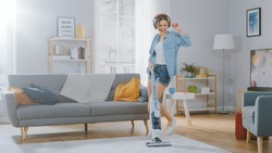 Shot of a Young Beautiful Woman in Jeans Shirt and Shorts Dancing and Vacuum Cleaning a Carpet in a Cozy Room at Home. She Uses a Modern Cordless Vacuum. She's Happy.