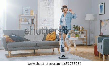 Shot of a Young Beautiful Woman in Jeans Shirt and Shorts Dancing and Vacuum Cleaning a Carpet in a Cozy Room at Home. She Uses a Modern Cordless Vacuum. She's Happy. Stockfoto ©