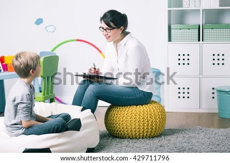 Shot of a young child psychologist talking with a boy