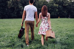 Shot of a young couple holding hands and finding a place for picnic. Selective focus.