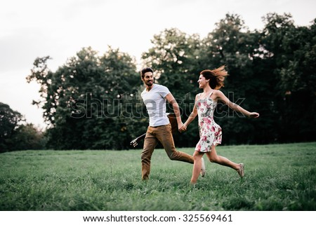 Shot of a young couple holding hands and running through the park. Blurry movement, soft focus