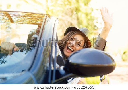 Shot of a young cute woman enjoying a drive in a convertible loving the breeze in her face waving with her arm  stock photo