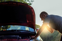 Shot of a young man calling roadside assistance after breaking down. Young adult Caucasian man talking on cell phone while analyzing his car after breakdown on the street. Car breakdown. Copy space.