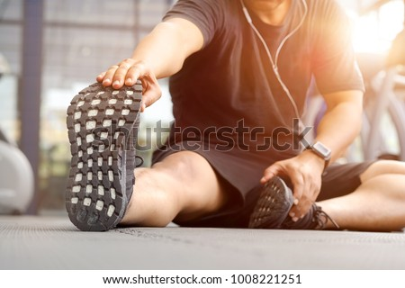 Shot of a young man stretching his legs before a gym workout