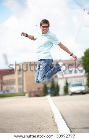Shot of a young man, that is jumping at the city street. He is happy. He is smiling.