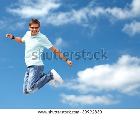 Shot of a young man, that is jumping on the sky background. He is happy. He is smiling.
