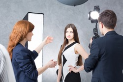 Shot of a young woman explaining a model what to do during the fashion photoshoot