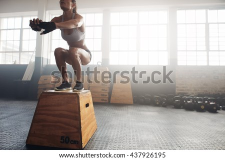Shot of a young woman jumping onto a box as part of exercise routine. Fitness woman doing box jump workout at crossfit gym. Stock photo ©