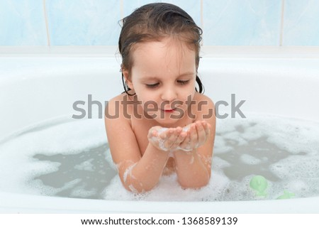 Shot of adorable baby girl with wet hair playing with soap foam in bath tub, has water procedure before sleaping, glad to be photographed, wasing alone in bathroom, looks at bubbles on her hands. #1368589139