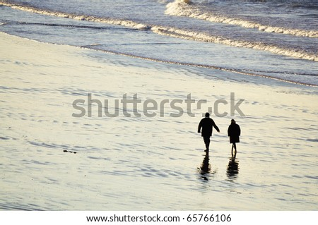 Shot of adult couple walking on the beach of Saint-Malo in brittany, france