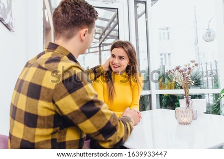 Shot of an affectionate couple sharing a romantic moment holding hands looking each other in the eyes smiling happily.