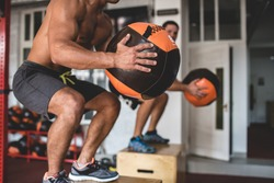 Shot of an athlete with a bare torso. Athletic-built man doing exercise with a medball. The athlete and his companion jump on the curbstone
