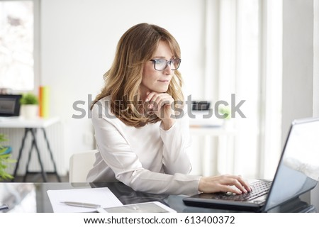 Photo of Shot of an attractive mature businesswoman working on laptop in her workstation.