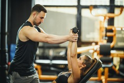 Shot of an attractive young woman working out with personal trainer at the gym.