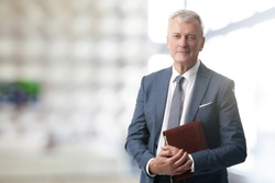 Shot of an elderly managing director with diary standing in conference room after business meeting.