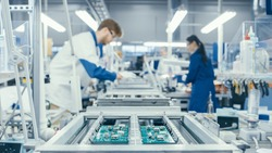Shot of an Electronics Factory Workers Assembling Circuit Boards by Hand While it Stands on the Assembly Line. High Tech Factory Facility.