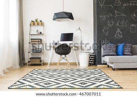 Shot of an elegant student room with a big blackboard and minimalist desk for work