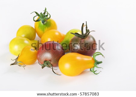 shot of assorted baby heirloom tomatoes on white - stock photo