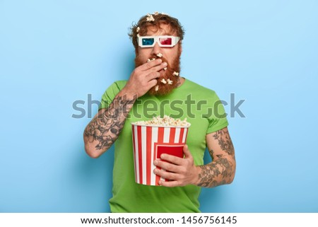 Shot of attractive ginger guy swallows fresh popcorn in cinema while watches exciting movie, wears three dimension glasses and casual green t shirt, all attention at screen, being attentive spectator Photo stock ©