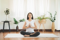 Shot of attractive healthy Asian woman doing yoga meditation at home in living room
