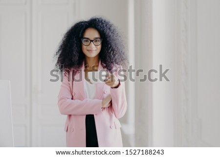 Shot of attractive woman with Afro hairstyle, drinks aromatic beverage, wears glasses, formal wear, poses in office over white background, copy space for your promotional content. People and business