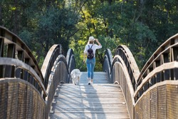Shot of attractive young amateur photograph woman walking with her dog crossing over a bridge in the park.