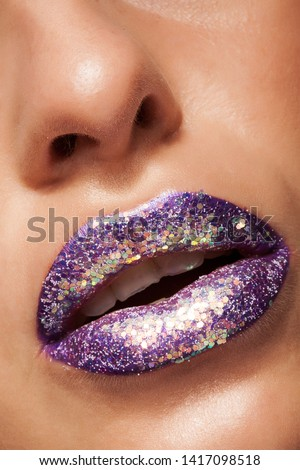 Shot of beautiful girl with purple lipstick and silver glitter.Sexy and stylish lips. Closeup of artistic lips. #1417098518