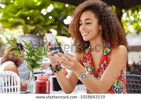 Shot of beautiful glad young female with Afro hairdo, types number of credit card on smart phone, makes purchase online or checks bank account, recreats in outdoor cozy cafe with fresh cocktail