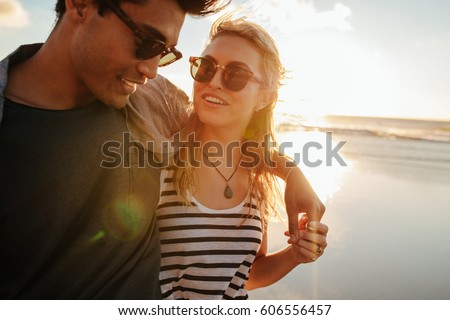 Shot of beautiful woman with her boyfriend on the beach on a summer day. Loving couple on summer holiday.