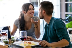 Shot of beautiful young couple sharing single spaghetti getting closer to kissing in the kitchen at home.