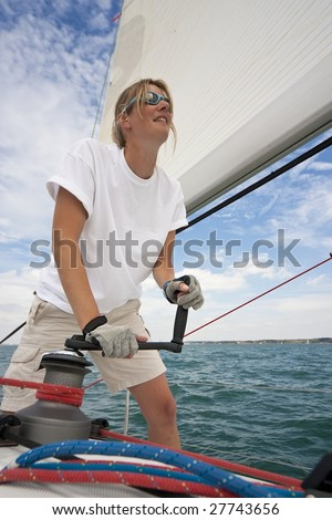 Shot of beautiful young woman on the deck of a boat operating a winch to hoist a sail