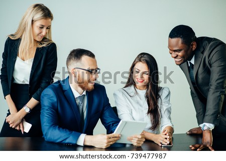Shot of business professionals having a meeting in office using digital tablet. Business partners using touchscreen computer for project discussion. #739477987