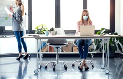 Shot of business young women wearing a hygienic facial mask working in the office while keeping safe distances.