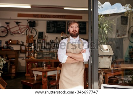 Shot of cafe owner standing proudly in the doorway of his restaurant. Young man wearing an apron standing with his arms crossed at the door of a cafe.