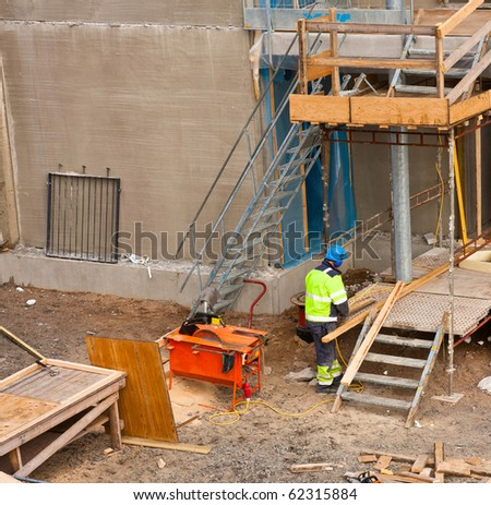 Shot of construction site with worker working wooden planks using  circular saw, chain saw and other tools