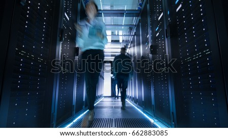 Shot of Corridor in Large Data Center Full of Walking and Working People. Pronounced Motion Blur.