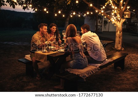 Shot of couples having an outdoor dinner party. Warm tones.