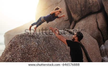 Shot of cute little boy leaping into his fathers arms from a big rock. Father and son enjoying summer holidays at the beach. #646576888