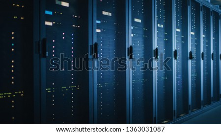 Shot of Dark Data Center With Multiple Rows of Fully Operational Server Racks. Modern Telecommunications, Cloud Computing, Artificial Intelligence, Database, Supercomputer. Blue Neon Light.