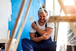 Shot of exhausted painter suffering from pain in his shoulder after working hard isolated on bright background. Portrait of a man at work suffering from shoulder pain. Stressed man holding shoulder.